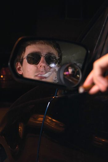 Reflection of man exhaling smoke on car side-view mirror