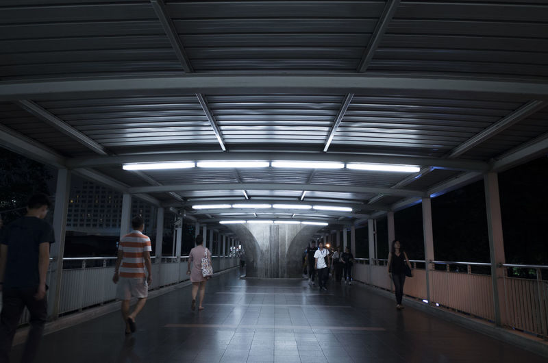 Illuminated Architecture Indoors  Transportation Ceiling Group Of People The Way Forward Public Transportation Direction Lighting Equipment Walking Built Structure Real People Men Diminishing Perspective Mode Of Transportation Subway Women Lifestyles Fluorescent Light Flooring Light
