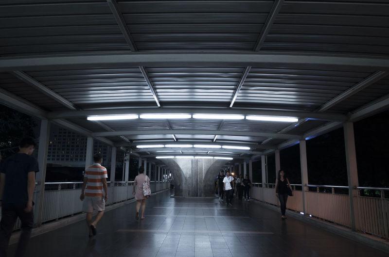 People walking in illuminated footbridge at night