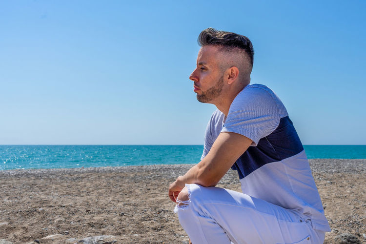 Man wearing sunglasses on beach against blue sky