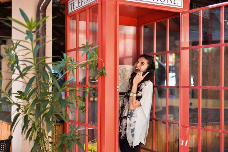 Woman talking on telephone while standing in booth