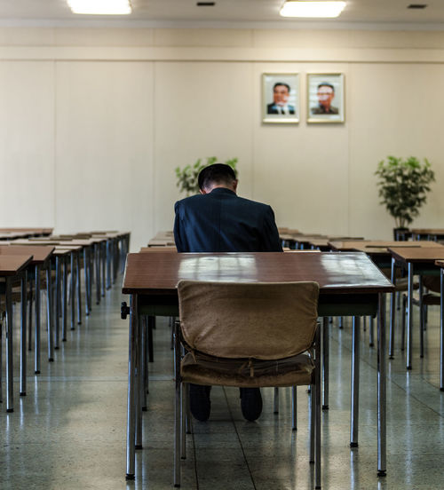 Man studying in central library, Pyongyang. Chair Classroom Communism Education Flower Great Leader Indoors  Kim Il Sung Kim Jong Il Men One Person People Real People Shadow Sitting Study