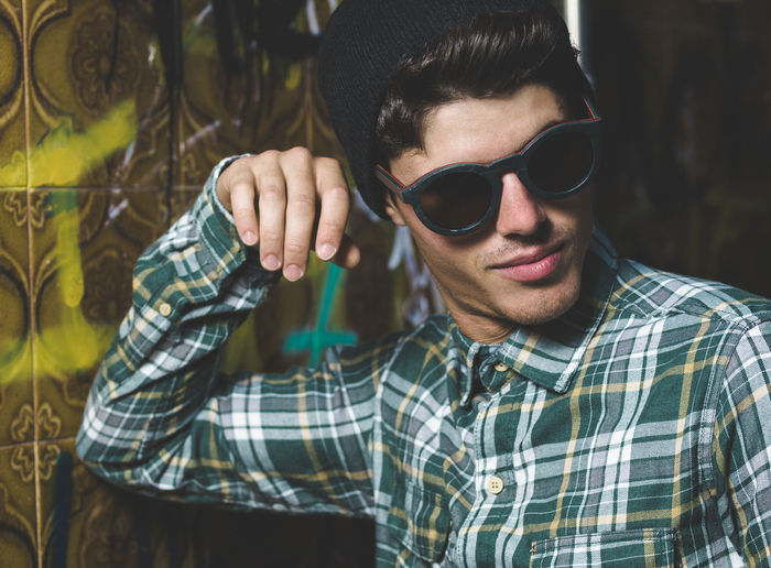 Young man wearing sunglasses standing by wall
