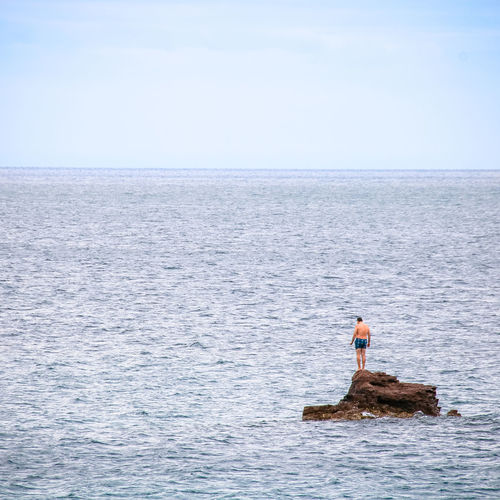 Mid distance of shirtless man standing on rock in sea against sky