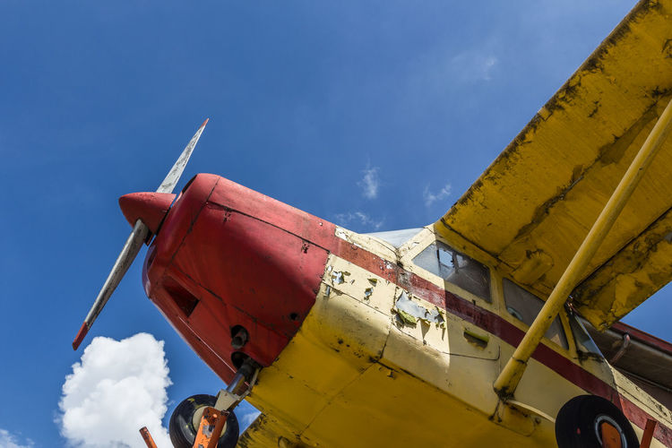 Vintage airplane seen from below, with blue sky in the background Abandoned Aeroplane Air Airplane Antique Aviation Blue Broken Decay Dirty Engine Flight Fly Fuselage Glory Historic Jet Old Plane Red Retro Rushing Rust Transportation Vintage