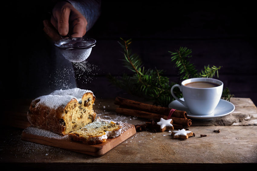 christmas cake, in germany christstollen and sprinkling powdered sugar from a sieve in a woman hand, coffee cup, spices and cinnamon star cookies on a rustic wooden table, dark vintage background with copy space Christmas Coffee Dark Rustic Baking Cake Christstollen Day Food Food And Drink Freshness Hand Human Hand Indoors  Motion Powdered Sugar Sieve  SLICE Sprinkling Table