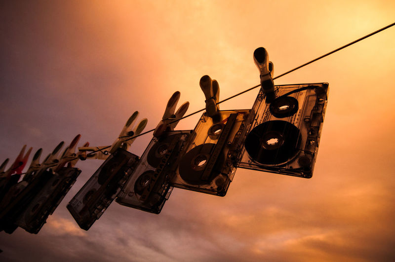 Low Angle View Of Audio Cassettes Hanging From Clothesline Against Cloudy Sky During Sunset