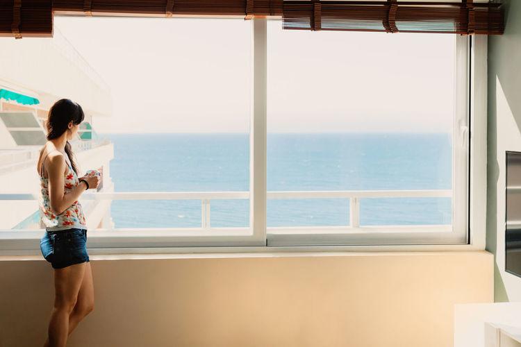 Woman having coffee while looking at sea through window