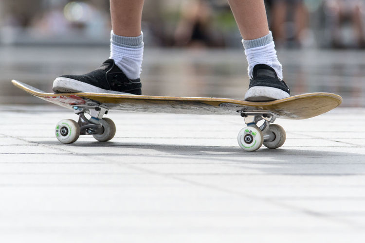Low section of person skateboarding on footpath