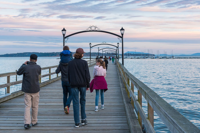 White Rock, British Columbia/Canada - September 8, 2016: city of White Rock and waterfront viewed from the historic pier. The beach, pier, and waterfront shops are a popular tourist destination. Beautiful British Columbia, Canada Family Holiday Pier Tourisme Tourists Traveling White Rock Pier Editorial Photography Evening Historic June Landmark Landmark Leisure Ocean Outdoors Pacific Ocean People Sunset Vacation Walking Around The City  Walking Pier Waterfront