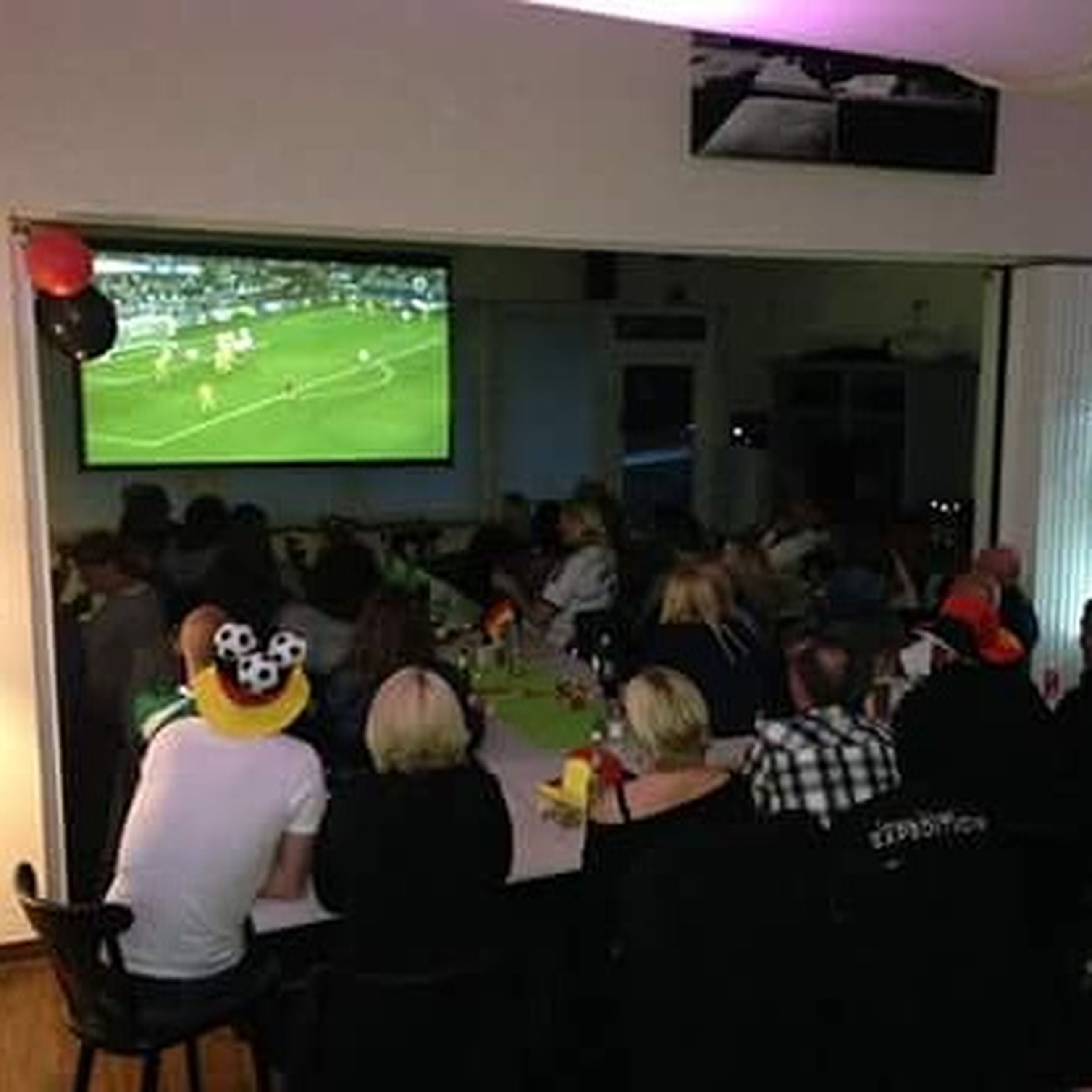 lifestyles, indoors, leisure activity, togetherness, men, person, casual clothing, celebration, sitting, holding, table, food and drink, bonding, enjoyment, friendship, large group of people, waist up, standing