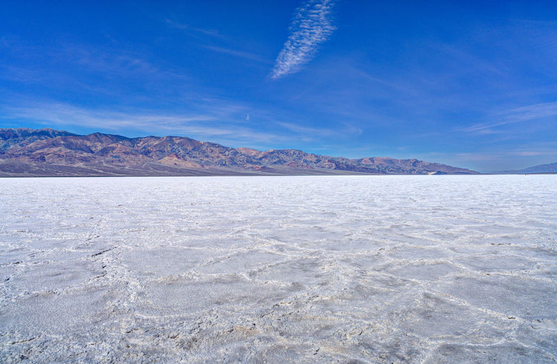 View of badwater basin at death valley national park against blue sky