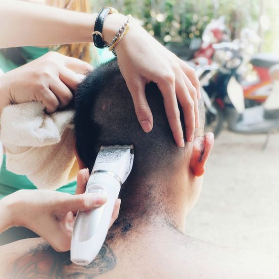 Cropped hands of person shaving man head