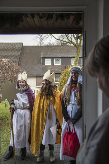 Brilon, Germany – January 6th 2018: Three holy kings - three girls stand at the doorstep as the Three Wise Man and collect donations Caspar Children Christianity Entrance Epiphany Holiday January 6th Man Melchior Singing Tradition Balthasar Bless Blessing Collect Costume Holy Kings Oriental Religion Royal Meeting Sacred Star Singers Three Wise