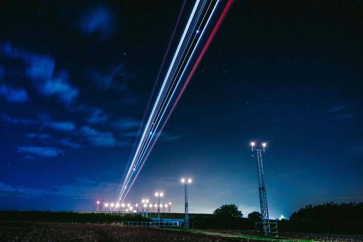 EyeEmNewHere Landing Lights Lines London Nightphotography Plane Airport Astronomy Beauty In Nature Blue Cloud - Sky Electricity  Illuminated Illumination Landscape Low Angle View Nature Night No People Outdoors Scenics Sky Star - Space Star Trail