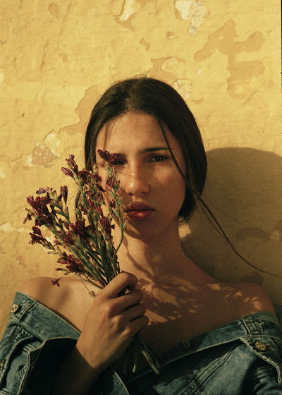 Portrait of woman holding flower against wall