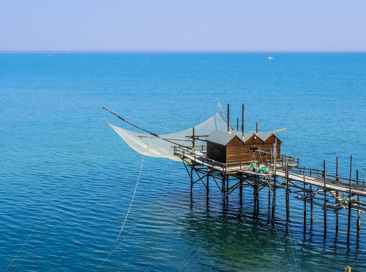 "Fishing system with ""balance"" Beauty In Nature Blue Color Blue Sea Blue Sky Clear Sky Day EyeEmNewHere Fishing Fishing Net Fishing Time Horizon Horizon Over Water Nature No People Outdoor Pillars Support Sea Sky Tranquil Scene Tranquility Water Waterfront Wood - Material Wooden Pier Wooden Pillars"