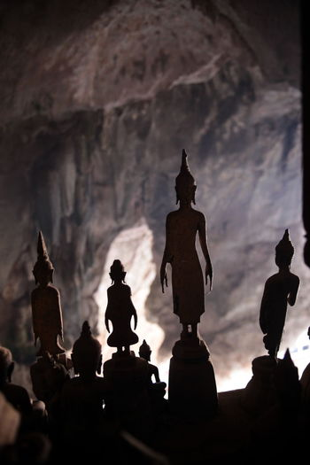 Close-up of silhouette buddha statues at pak ou caves