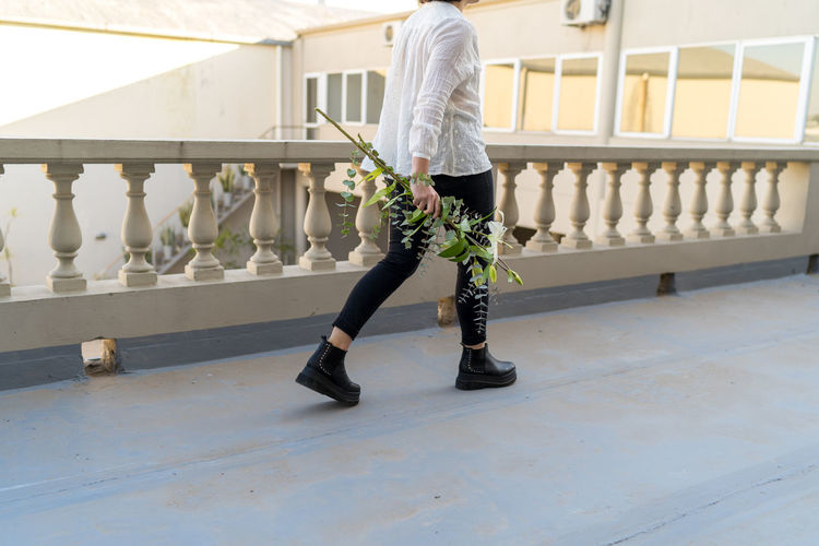 Young woman from back walking with bouquets of white flowers
