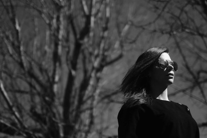 Light And Shadow Monochrome Black And White Real People One Person Lifestyles Fashion Tree Young Women Focus On Foreground Leisure Activity Women Outdoors Standing Young Adult Beautiful Woman Bare Tree Branch Day Nature Adult People