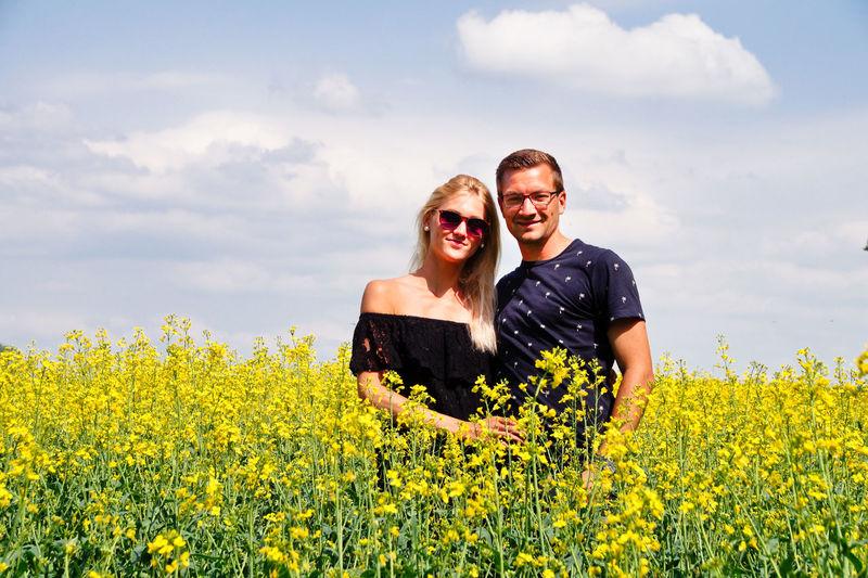 Portrait Of Couple Standing Amidst Yellow Flowers On Oilseed Rape Field
