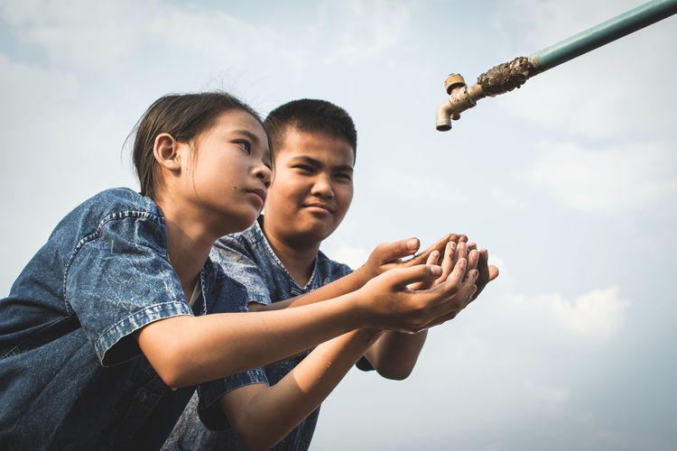 Siblings With Hands Cupped Below Tap Against Sky