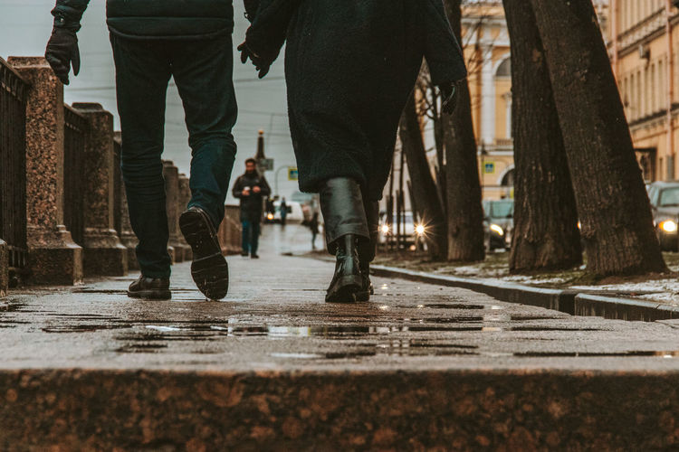 Low section of couple holding hands walking on wet street in city