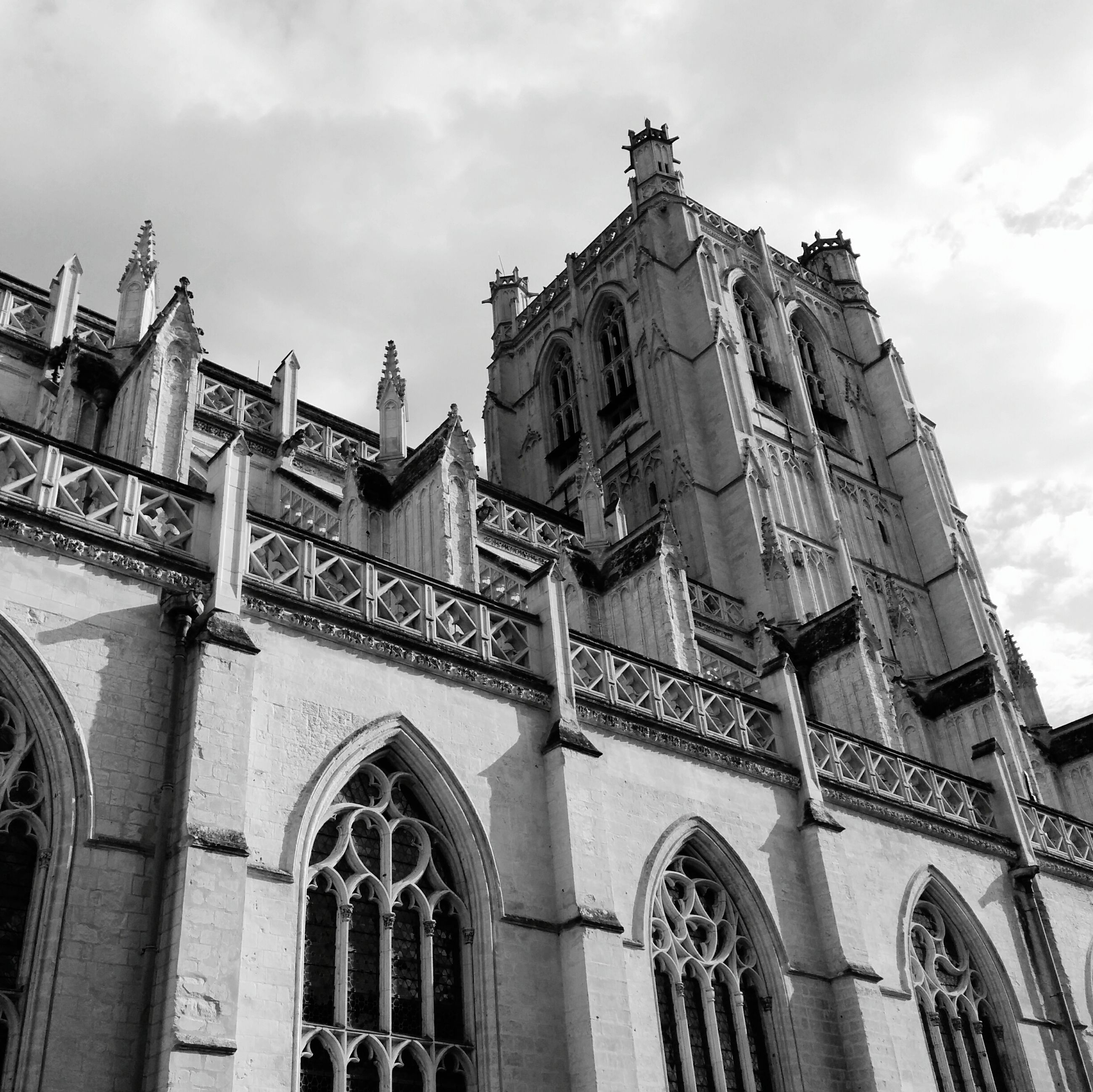 architecture, built structure, building exterior, low angle view, arch, sky, religion, cloud - sky, church, history, facade, place of worship, window, cloud, city, day, cloudy, old