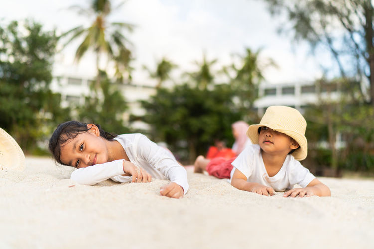 Siblings lying on sand at beach