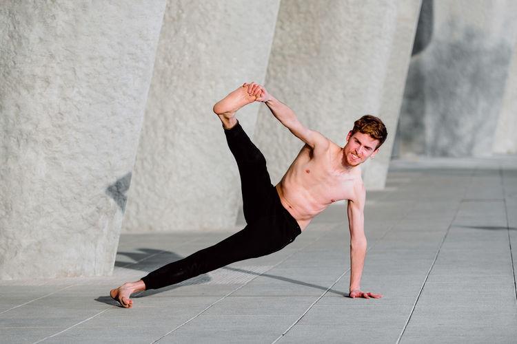 Young shirtless man exercising outdoors