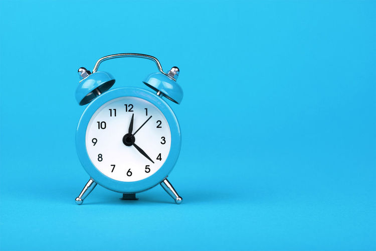 Vintage retro styled twin-bell alarm clock over blue background Checking The Time Turquoise Colored Minute Hand Bell Metal Close-up Deadline Still Life Number Single Object No People Colored Background Copy Space Studio Shot Clock Time Alarm Clock Blue Blue Background Indoors  Clock Face Night Late Retro Styled
