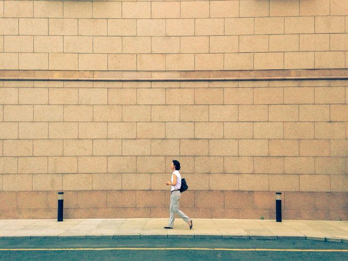 Full length of young man standing on wall
