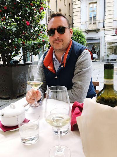 Portrait of man having wine while sitting at sidewalk cafe