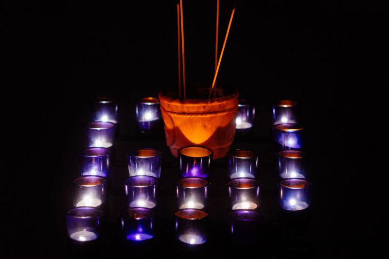 Close-up of illuminated candles over black background