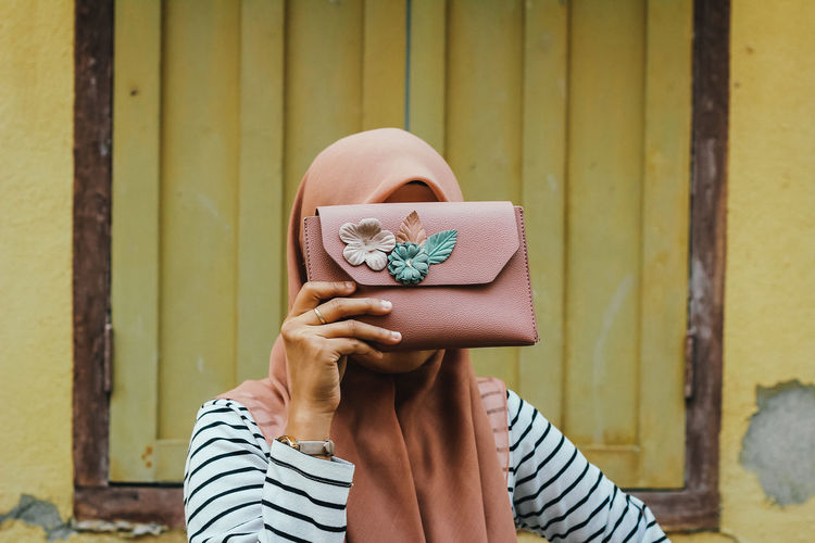 Woman holding purse over face against wall