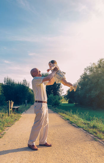 Senior man playing with adorable baby girl over a nature background. Grandparents and grandchild leisure time concept. Family Outdoors Nature Togheter Love Affectionate Summer Generations Walking Path Two People Vertical Togetherness Positive Emotion Grandfather Granddaughter Grandparent Playing Care Protection Senior Elderly Old Holding Embracing