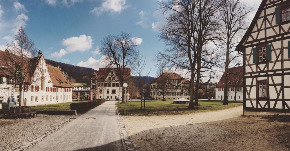 Empty road amidst buildings against sky on sunny day at blaubeuren