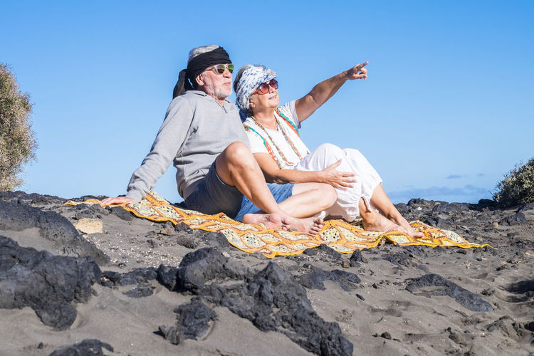 elderly couple hippie style sitting on the beach with sunglasses and looking away Adult Beach Bonding Casual Clothing Clear Sky Couple - Relationship Day Elderly Couple Emotion Full Length Hippie Style Leisure Activity Lifestyles Nature Outdoors People Positive Emotion Retirement Sitting Sky Smiling Sunlight Togetherness Two People Women