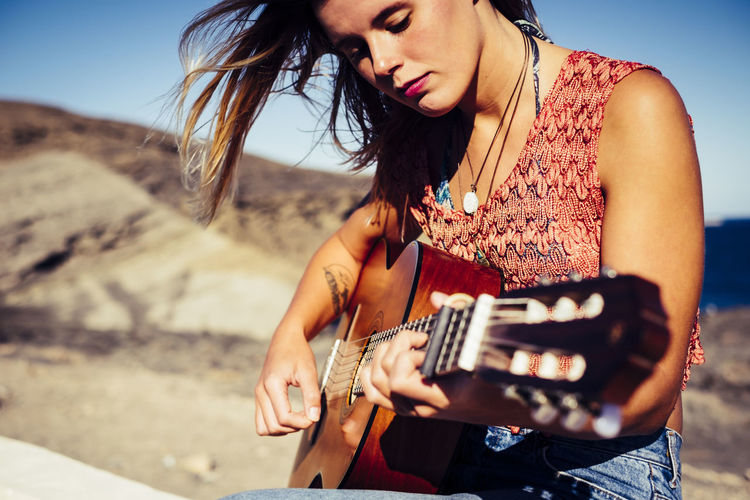 nice caucasian blonde girl playing guitar outdoor in Tenerife Playing Guitar Adult Camera - Photographic Equipment Casual Clothing Close-up Day Guitar Hippie Holding Leisure Activity Lifestyles Music Musical Instrument Musician Nature One Person Outdoors People Photography Themes Playing Real People Sand Sky Young Adult Young Women