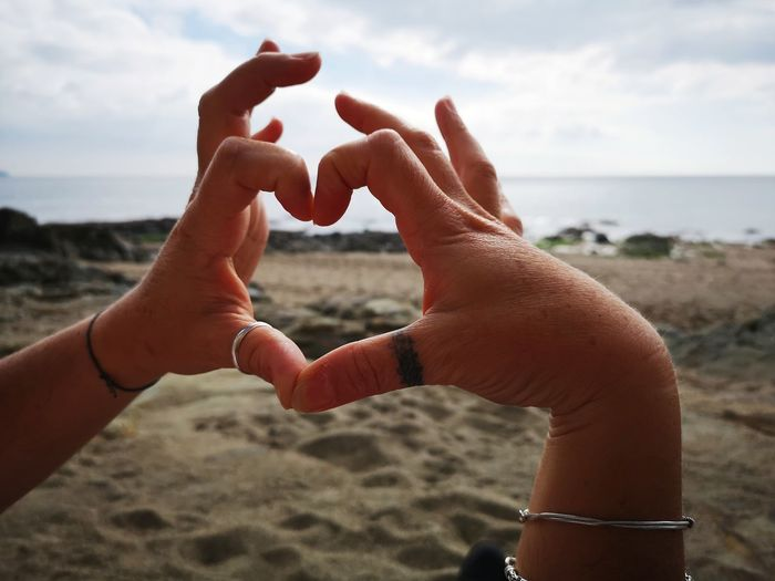 hands and hearts Close-up Send Love Into The World Framing The Subject Hands Fingers Making A Heart Shape Thumb Tattoo Soft Focus Human Hand Water Sea Beach Sand Close-up Sky Horizon Over Water Wrist Thumb Fingernail Joint - Body Part Coastline Shore Personal Perspective 2018 In One Photograph #NotYourCliche Love Letter