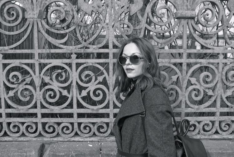 Side View Close-Up Of Woman Wearing Sunglasses While Standing By Fence