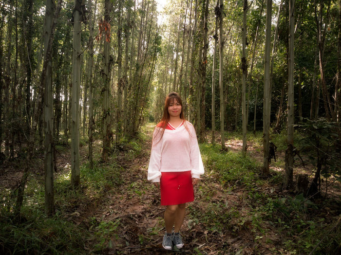 Portrait of mid adult woman walking on field amidst trees in forest