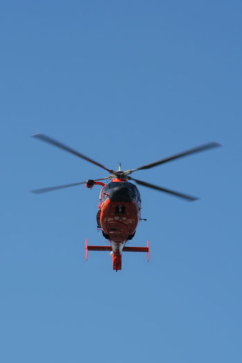 Low angle view of helicopter flying against clear blue sky