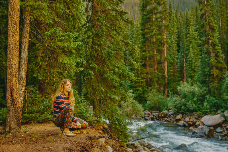 Woman sitting by stream in forest