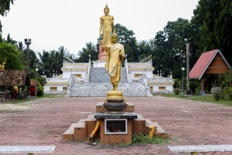 Wat Pikulthong Standing Buddha in Tumpat, Kelantan Budhism Budhist Temple Buddhist Temple Sculpture Statue Art And Craft Architecture Human Representation Male Likeness Built Structure Representation Tree Religion Belief Plant Spirituality Creativity Day Place Of Worship Building Gold Colored No People Idol