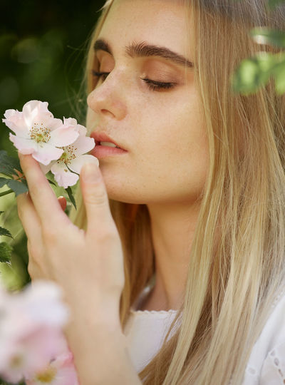 Close-up portrait of woman holding flower