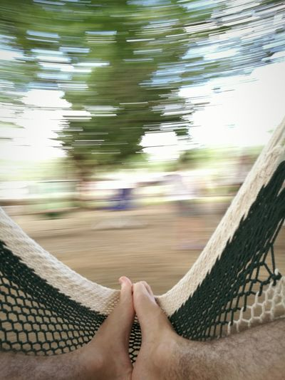 Low section of man relaxing in hammock