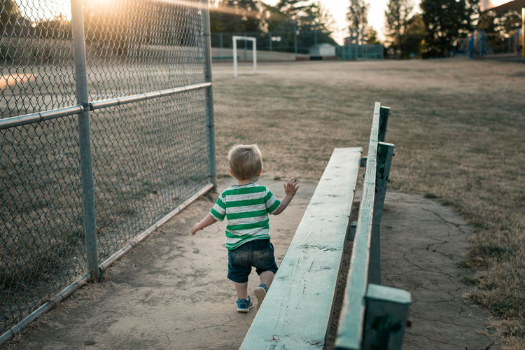 Boy running by baseball field bench Child Playing Child Running Bench Fence Grass Baseball Field Toddlerlife Toddler  Happiness Inspiration Dream Daydreaming Baseball Outdoors Innocence Sport Playing Boys Child Childhood Dirt Playing In Dirt