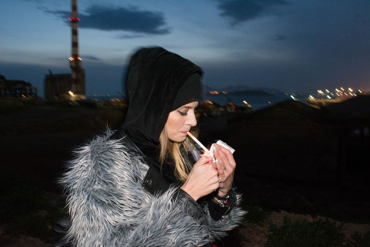 Young Woman Lighting Cigarette In City Against Sky At Night
