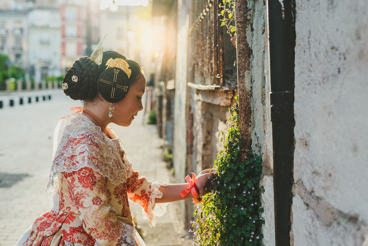 Side view of girl touching plants against wall